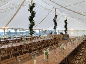 Traditional Marquee for minimalist wedding with fairy lights and floral king poles