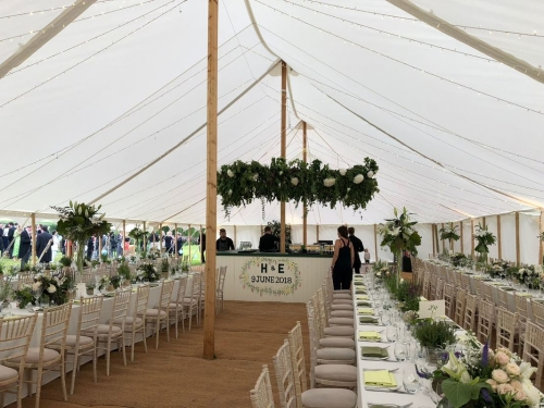White wedding with floral hanging hoop and circular bar
