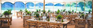 Traditional wedding marquee with rustic tables and chairs with green foliage and windows
