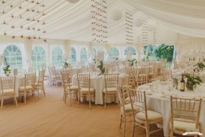 Neutral garden marquee wedding with lily centrepieces and flying birds