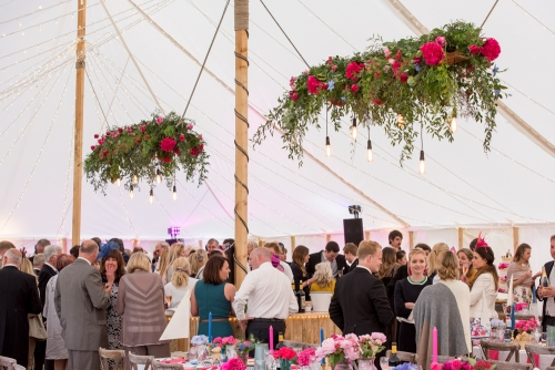 Pink and blue marquee wedding with hanging floral and festoon lights