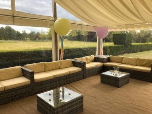 Clear span marquee with clear windows, rattan furniture and balloons